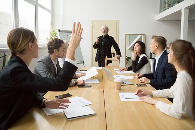 Businesswoman raising hand asking senior coach questions