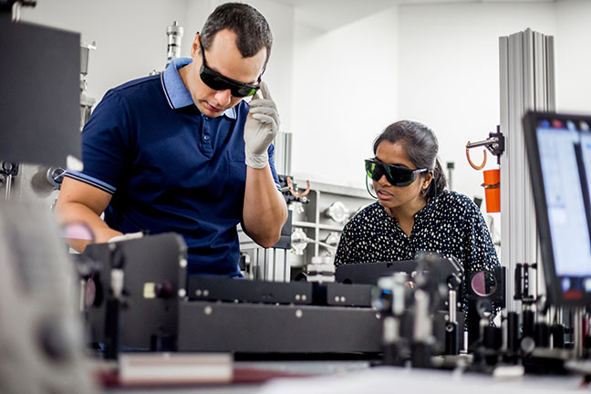 Mentor Explaining to a Student How to Use Powerful High Frequency Laser